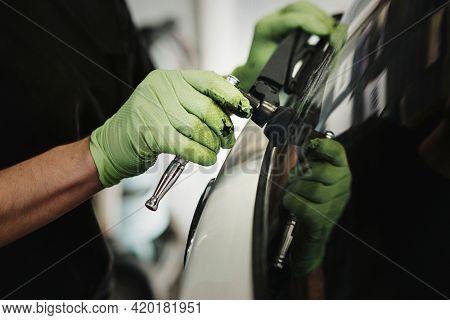 Mechanic removing car wiper arm