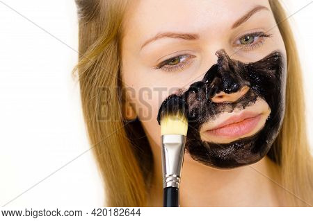Young Female Being Apply With Brush Charcoal Mask, Black Detox Mud To Her Face. Girl Taking Care Of