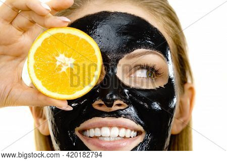 Woman With Carbo Detox Black Peel-off Mask On Face Holding Orange Fruit. Teen Girl Taking Care Of Oi
