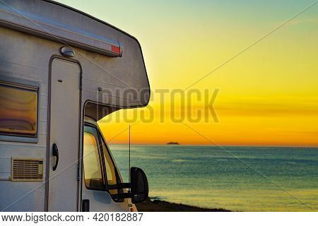 Camper Rv At Sunrise On Mediterranean Coast In Spain. Camping On Nature Beach. Vacation And Trip In