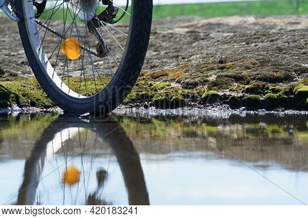 Bicycle Wheel In A Puddle. The Bike Moves Through The Puddles On A Rainy Day