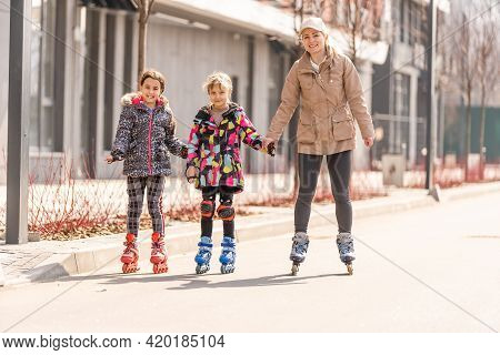 A Happy Family In Roller Skates, Mother Two And Two Daughters On Roller Skates