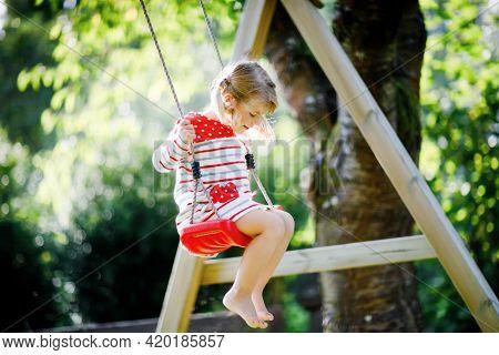 Happy Beautiful Little Toddler Girl Having Fun On Swing In Domestic Garden. Cute Healthy Child Swing