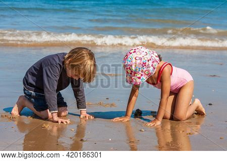 Two cute children little girl female child and boy male child kneeling playing in the sand together on a beach by the seaside