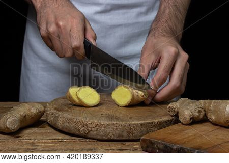 Ginger On A Wooden Background. The Chef Cuts The Ginger Root. Cooking Ginger. Healthy Food