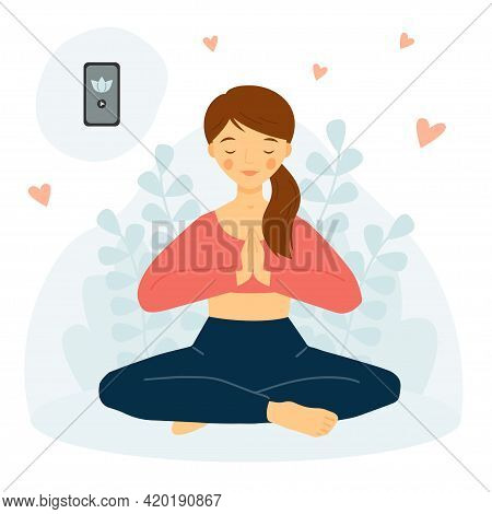 The Girl Practices Yoga With Phone. Meditation Concept. Yoga Mobile App. Girl In Lotus Pose. Namaste