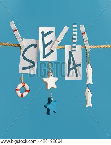 Summer Poster With Lettering Sea, Inscription On White Pieces Of Paper Hanging With Clothespins On R