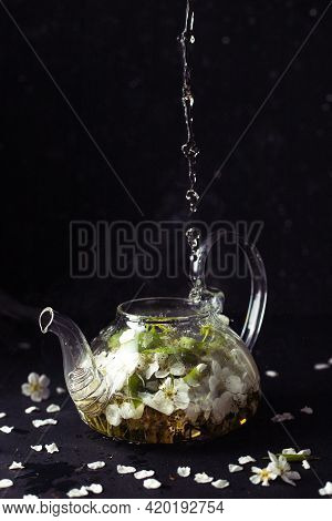 There Are Apple-tree Flowers In A Glass Teapot. The Hot Liquid Is Poured On Top To Make The Tea Brew