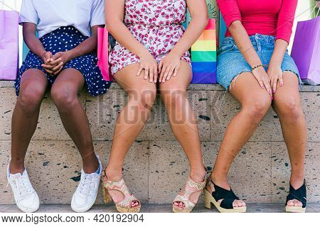 Midsection Of Three Girls Sitting On Stairs After Buying Presents. Happy Women Are Sitting Relaxed O