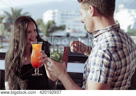 Happy Friends Having A Party Drinking Cocktails. Fashionable Teenagers Celebrating Holiday After End