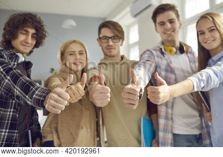 Close Up Of Hands Raised Up Thumbs Up Of Group Of Satisfied Young College Or University Students.