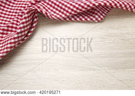 Red Checered Cloth On Wooden Table Top View. Picnic Towel On Light Wood Texture Background Empty Adv