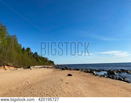 Sea Shore On A Summer Beach With Blue Water Waves And Sand With Rocks And Pebbles And Orange Sand Ro