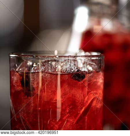 Close Up Of Glass With Red Berries And Mint Lemonade Drink On Backlit Blurred Background. Healthy Fr