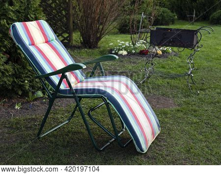 Chaise Longue And Alit Coals In Chargrill. In Expectation Of Barbecue. Idyllic Landscape