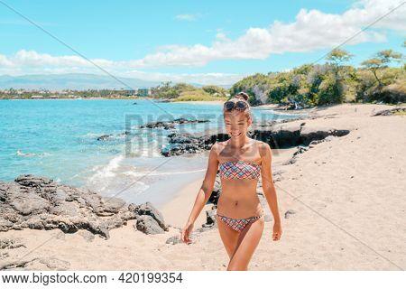Hawaii cove beach travel destination happy Asian tourist woman walkin relaxing by the ocean on warm summer sand. Sunbathing in bikini by the waves.