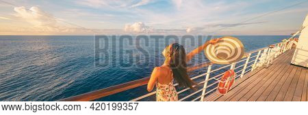 Happy cruise woman relaxing on deck feeling free watching sunset from ship on Caribbean travel vacation. Panoramic banner of sea and boat.