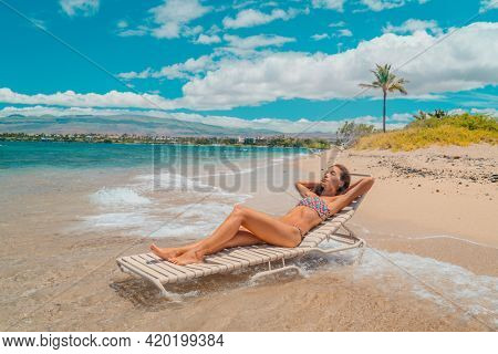 Beach vacation woman relaxing in bikini lying down on sun lounger sunbathing with chair in the waves of the ocean in Hawaii. USA Hawaiian island travel lifestyle summer vacation.