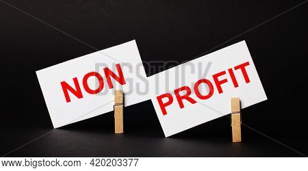 On A Black Background On Wooden Clothespins, Two White Blank Cards With The Text Non Profit