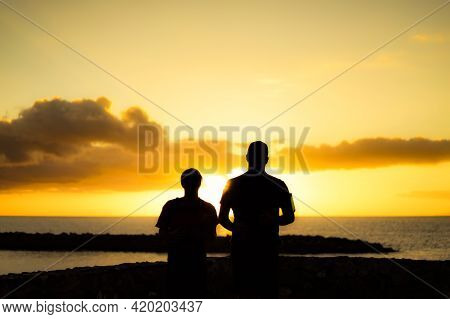 Silhouette Watching Sunset On The Beach. Relax And Sunset Concept.