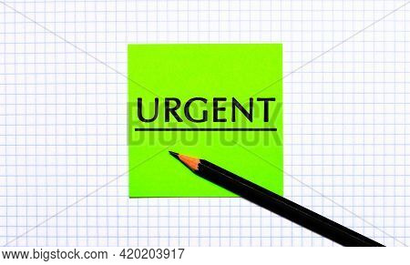 There Is A Green Sticker With The Text Urgent And A Black Pencil On The Checkered Paper.