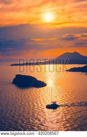 Aegean Sea with Greek islands view on sunset with yacht in sea. Cape Sounion, Greece