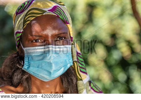 African middle aged woman, female in Africa, wearing traditional clothes and face mask in Coronavirus COVID-19 pandemic
