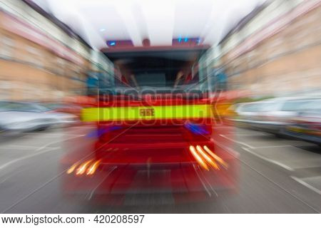 Motion blurred fire engine tender fire brigade vehicle moving at speed on a road through cars traffic and buildings