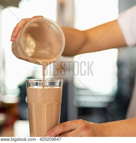 Sweet Chocolate Milkshake. Chef Pours Cocktail From Shaker Into Glass Against Window On Blurred Back