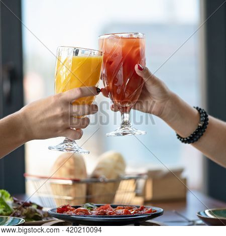 Festive Toast. Female Friends Clink Glasses With Fresh Juice Or Soft Drink Against The Window On A B