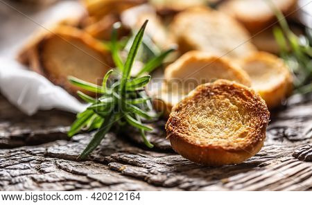 Crunchy And Savory Bake Rolly With Goldish Color Served In The Paper With Fresh Green Rosemary.