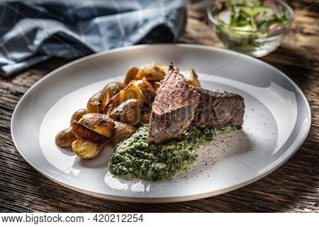 Delicious Grilled Beef Sous Vide Steak Served On A White Plate With Crunchy Roasted Potatoes, Spinac