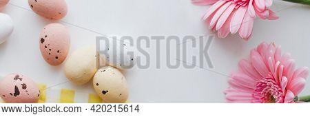 Chocolate Easter eggs and pink gerbera flowers flatlay