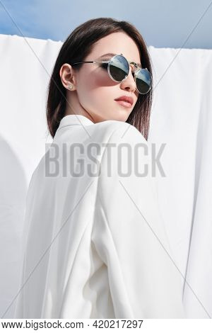 Fashion shot. Beautiful young woman model posing outdoor in white clothes and sunglasses among white fabrics fluttering in the wind. Summer style.