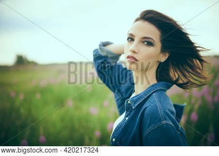 Portrait of a beautiful brunette girl in denim clothes standing in a valley against cloudy sky. Beauty, fashion. Denim style.