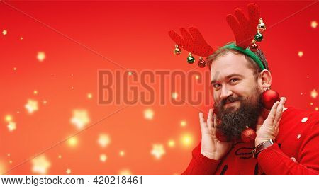 Portrait of a funny hipster man with a beard decorated with Christmas balls smiling at camera.Modern hipster Santa Claus.  Red background  in stars with copy space.