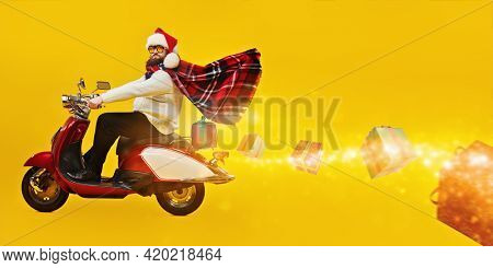 Cheerful fat man in Santa Claus hat rides a red scooter carrying gifts for Christmas and New Year. Bright yellow background with copy space. Modern hipster Santa Claus.