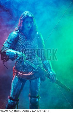 Beautiful and brave medieval female knight in armour with a sword on a dark hazy background.