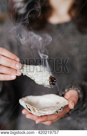 Woman burning sage smudge to cleanse the house