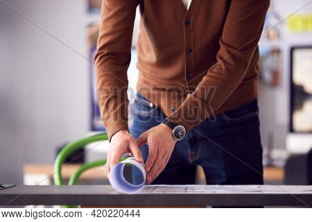Close Up Of Male Architect In Office Unrolling Building Plan Or Blueprint On Desk