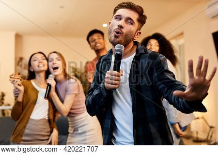 Love Singing. Enthusiastic Handsome Young Guy Singing With Microphone While Playing Karaoke With Fri