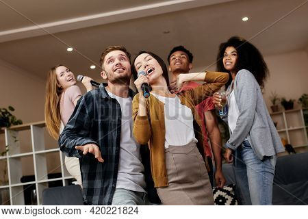 Party Time. Cheerful Young Friends Holding Microphone And Singing Together While Playing Karaoke Wit