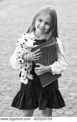 Adding Fun To Study. Happy Child Hold Toy Dog And Books Outdoors. Back To School Supplies. Fashion U