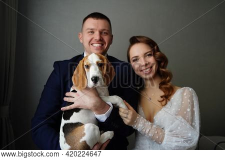 Couple Of Newlyweds With A Dog Beagle. Pets On Their Wedding Day.