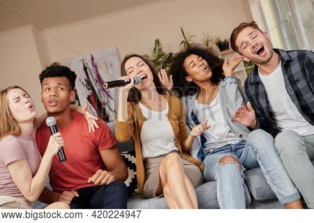 Sing As You Can. Enthusiastic Group Of Friends Singing With Microphone While Playing Karaoke At Home