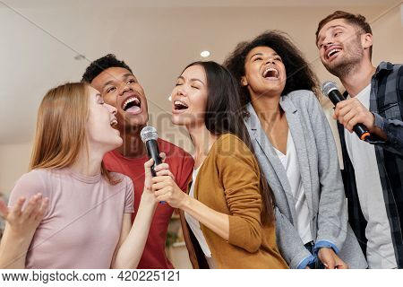 Singing For Everyone. Cheerful Multicultured Friends Singing With Microphone While Playing Karaoke A