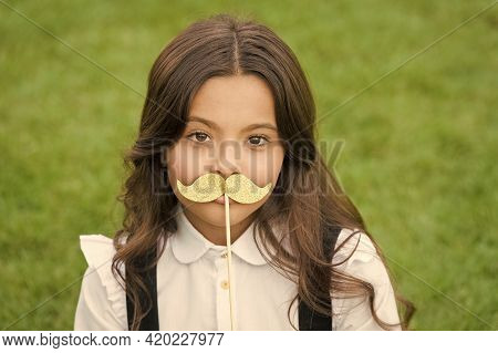 Funny Party Concept. Little Child School Uniform. Back To School. Small Schoolgirl Sit On Green Gras