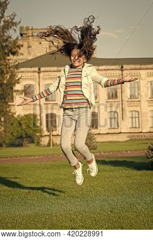 Happy Kid Jumping High. Sense Of Freedom. Childhood Happiness. Small Girl With Curly Hair Jump Outdo