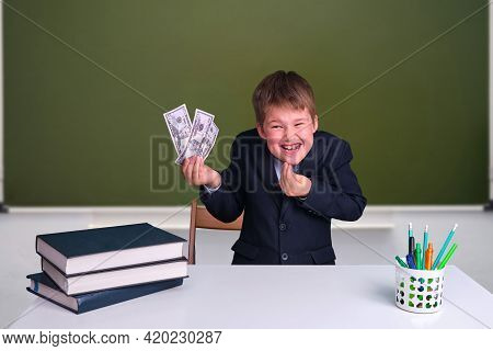A Cunning Boy With Money In His Hands At A Desk In A School Classroom. Us Dollars In Junior's Hand O