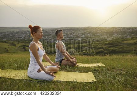 Man And Woman Meditating In Countryside At Sunset
